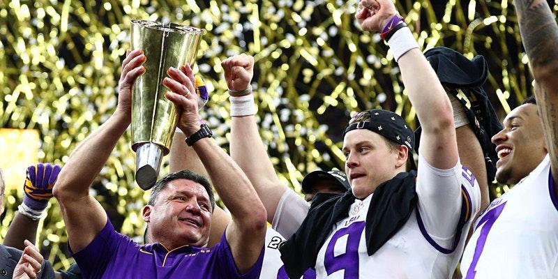 LSU coach holding trophy